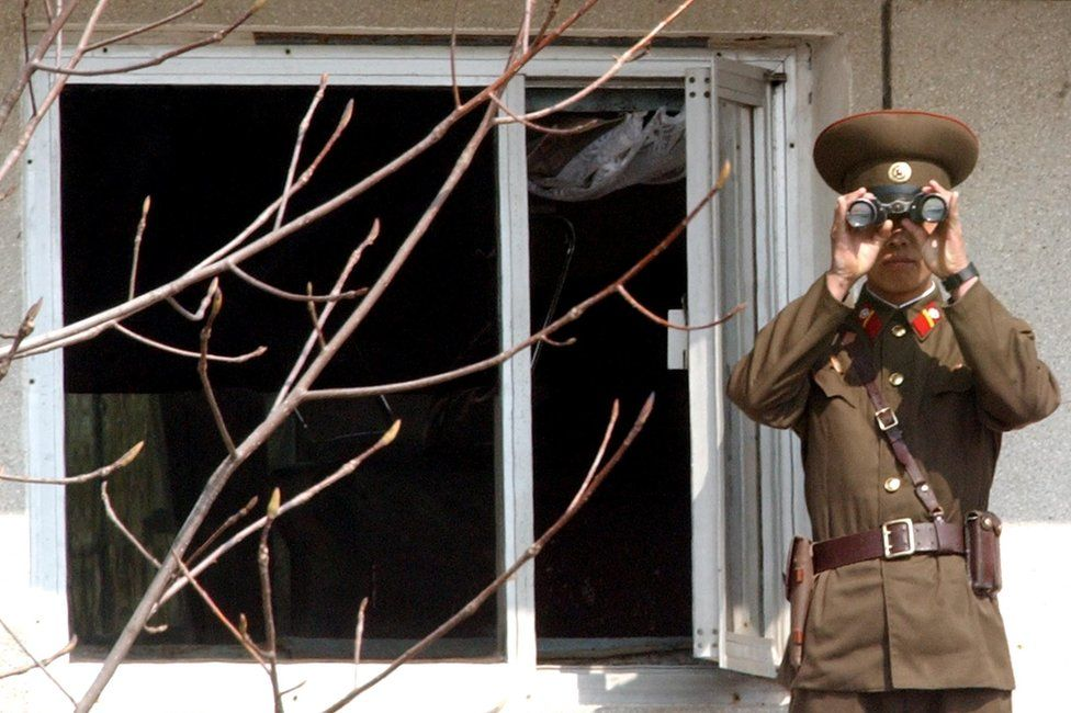 A North Korean soldier looks at the southern side through field glasses at the border village of Panmunjom, north of Seoul, Wednesday, 13 April 2005