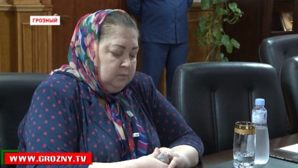 Yakha Beksultanova sits, head bowed, as a Chechen minister tells her to apologise spreading for false information