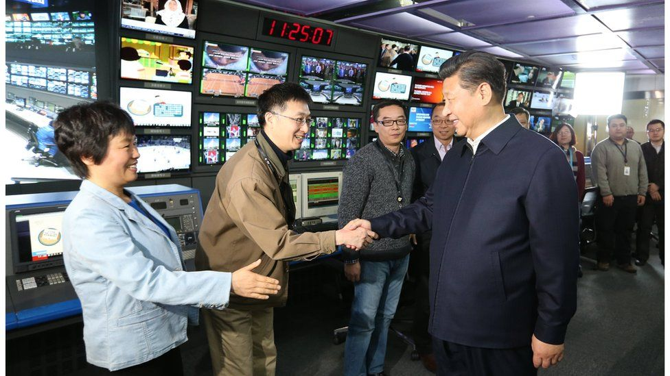 Chinese President Xi Jinping shakes hands with staff members at China Central Television