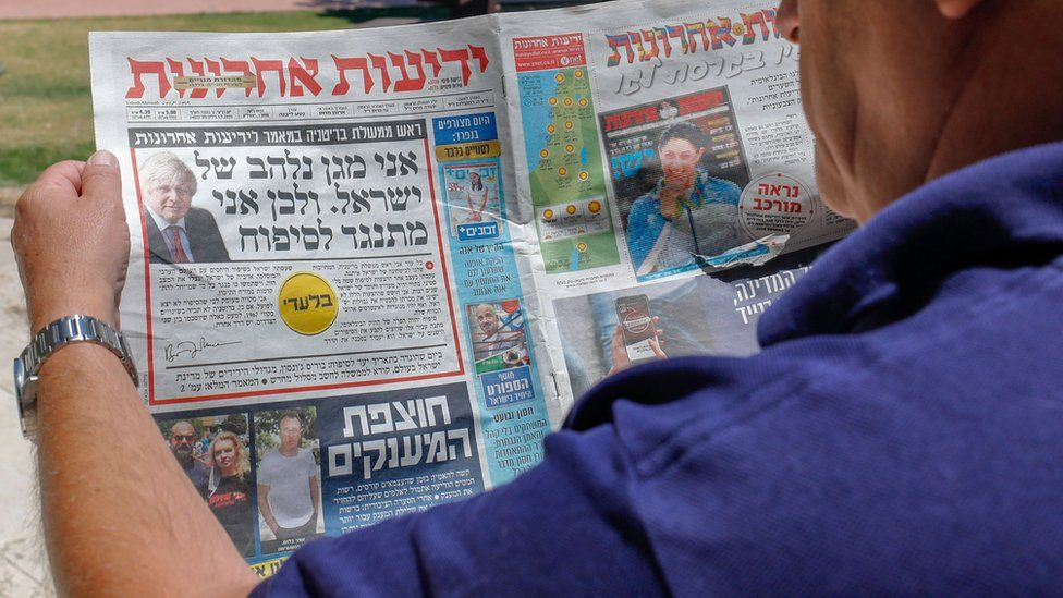 A man looks at an article by Boris Johnson on the front page of the Hebrew-language Israeli newspaper Yedioth Ahronoth (1 July 2020)