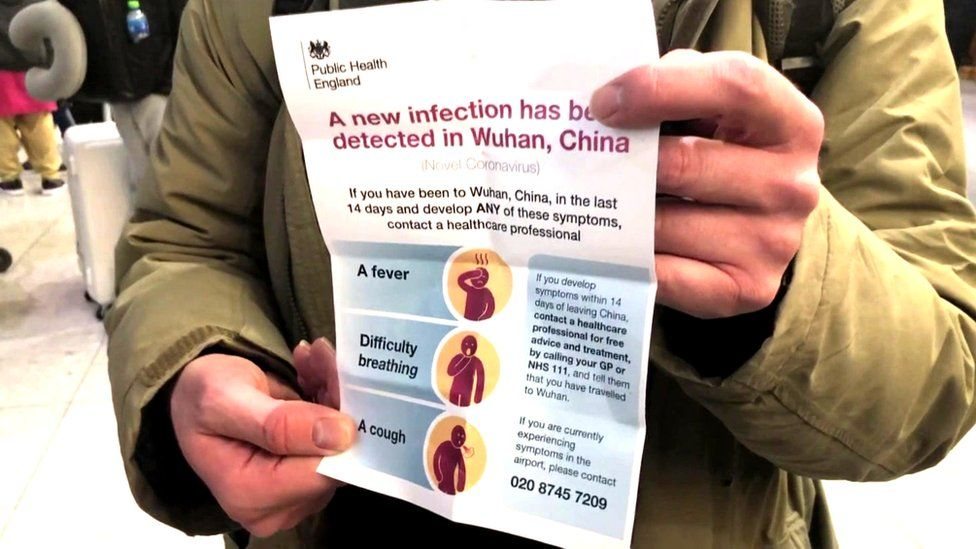 Passenger holding leaflet about the infection