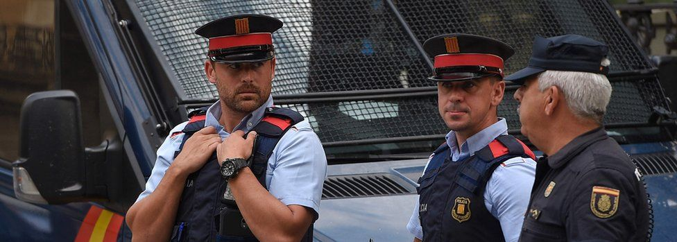 Catalan police, like these in Barcelona on the left, have been ordered to accept the command of Spain's Civil Guard (R)