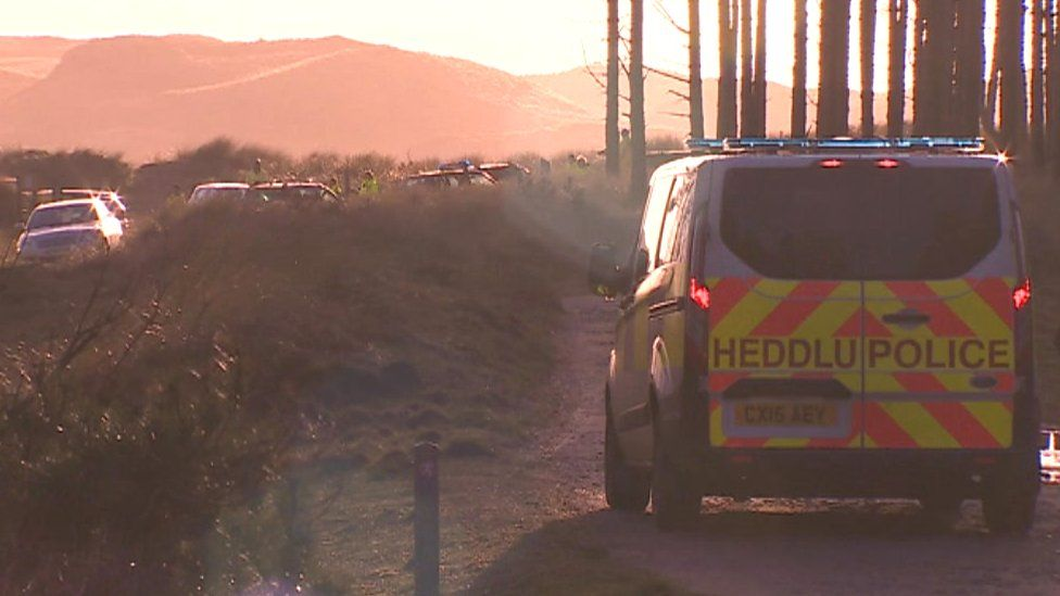 A police van at the beach following the discovery of the bodies
