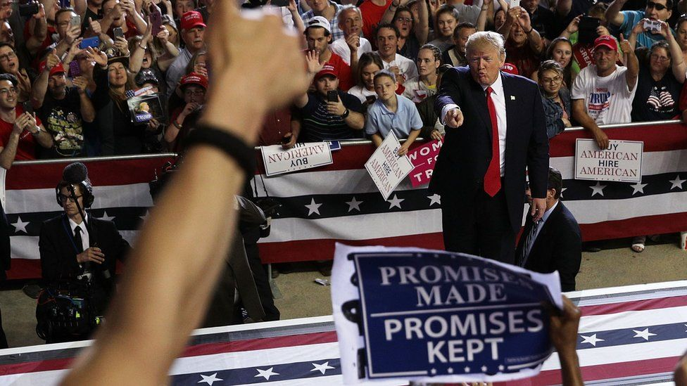 A photograph from a Trump rally shows him me pointing in direction of a supporter with a 'Promises made, promises kept' banner