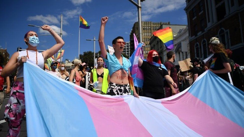 An activist march held outside with people carrying a huge flag for transgender rights
