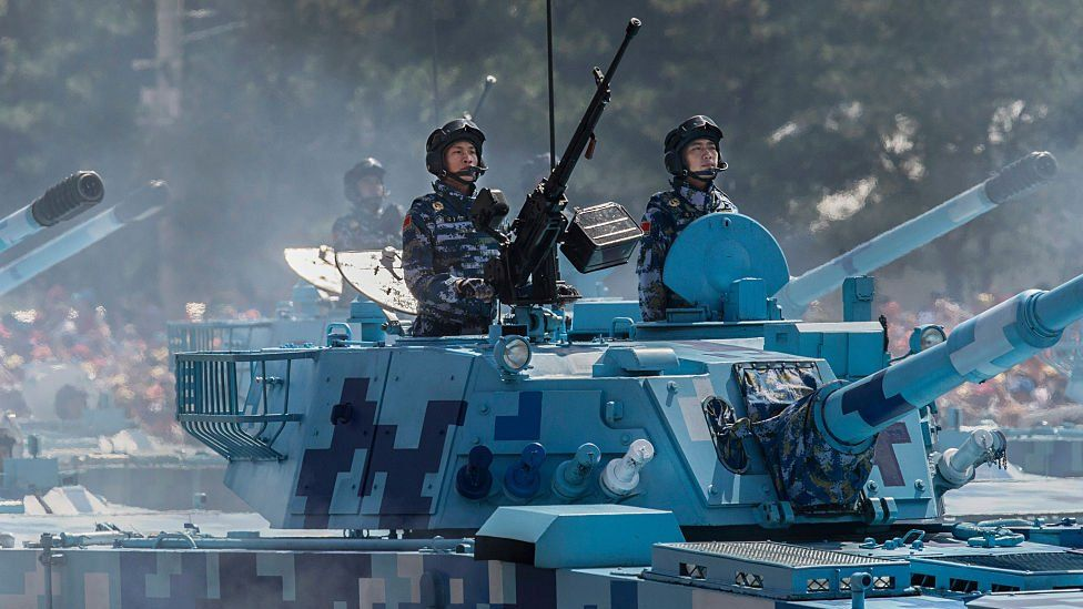 Chinese soldiers ride in tanks as they pass in front of Tiananmen Square and the Forbidden City