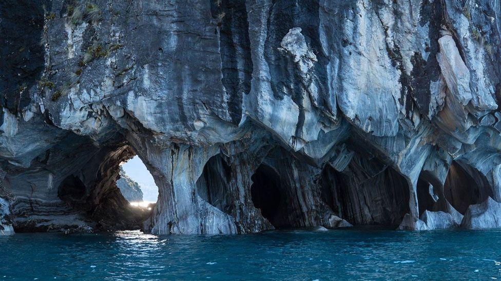 Cavernas con sus pies hundiéndose en el agua.