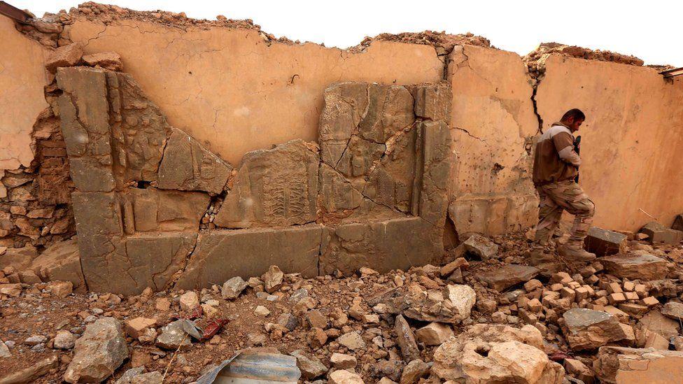 An Iraqi soldier walks past damaged Assyrian artefacts at Nimrud (15 November 2016)