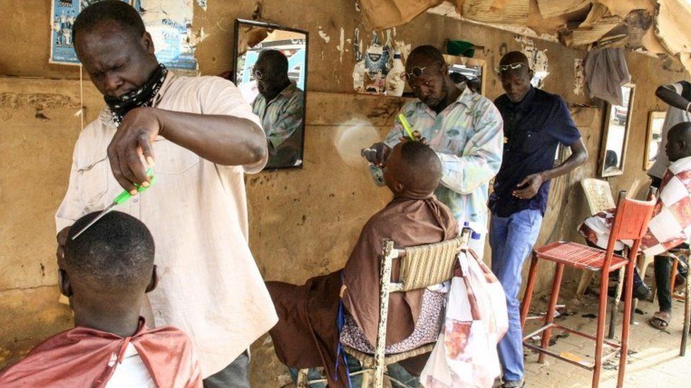 Men receive haircuts at a barbershop in the centre of the Sudanese capital Khartoum on August 22, 2019
