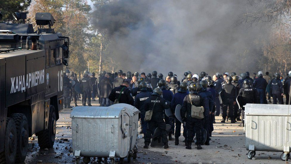 Bulgarian riot police stand near garbage bins during clashes in the migrants reception centre in the town of Harmanli