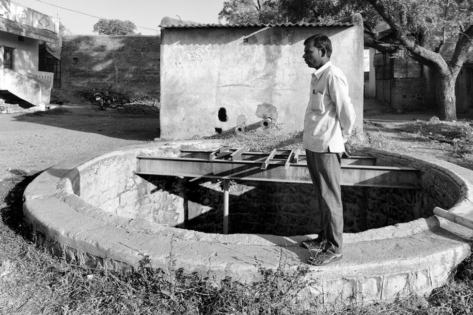 Namdev Kamble, Rajashree's father, standing over the well where his daughter slipped and fell.