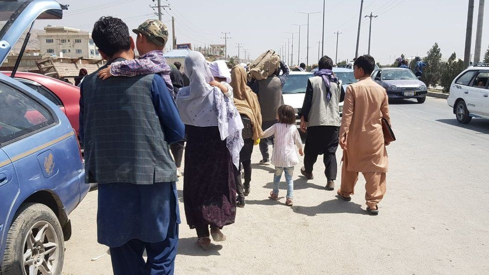 Afghans waiting outside Hamid Karzai International Airport on 21 August