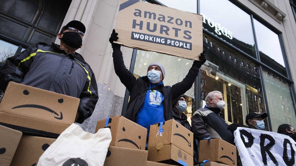 """People gather outside of the building where Amazon CEO Jeff Bezos owns an apartment for a protest against the company""""s treatment of its workers in New York, New York, USA, 02 December 2020"""