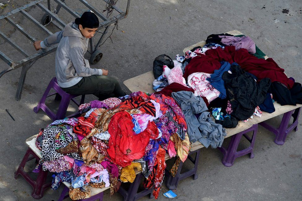 A Tunisian boy sells clothes at a market in the centre of Tunis on April 14, 2017. AFP PHOTO / FETHI BELAIDFETHI