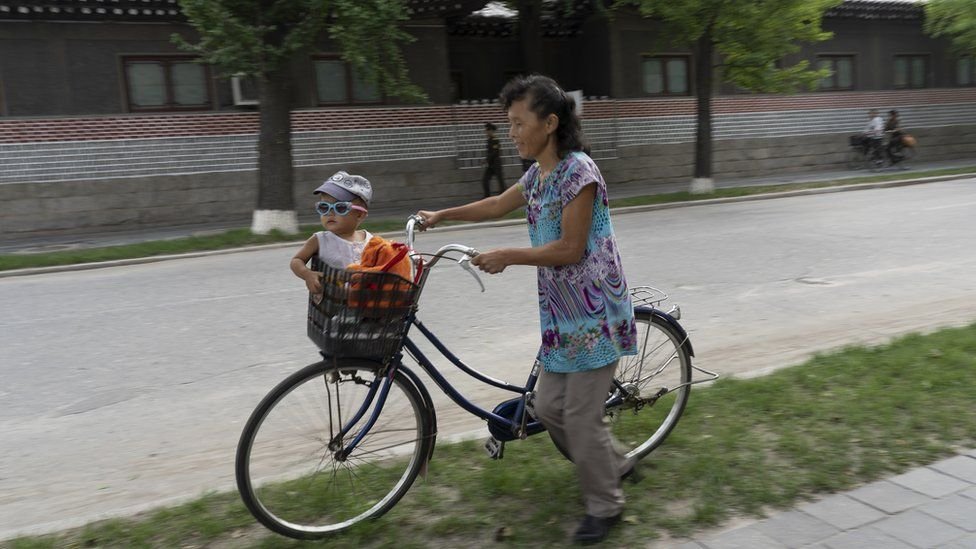 A mother watches her child, who sits in the basket of a bicycle