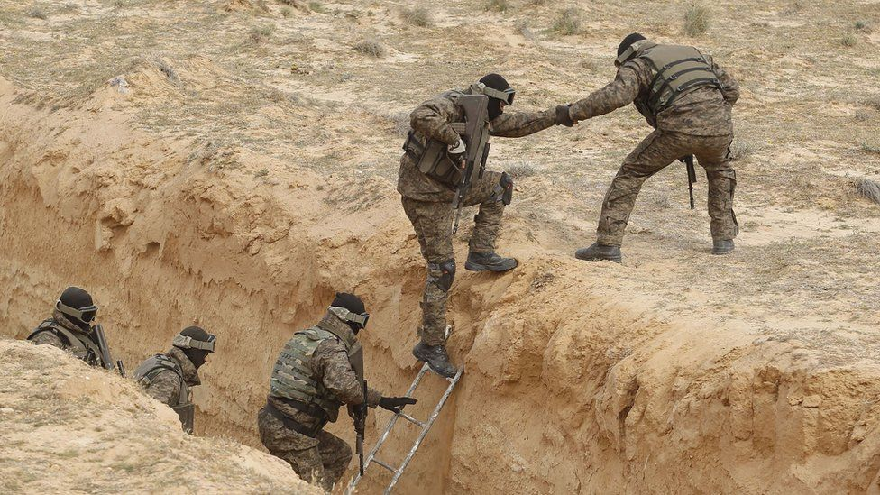 Tunisian soldiers participating in an exercise climb out of a trench, that forms part of a barrier along the frontier with Libya
