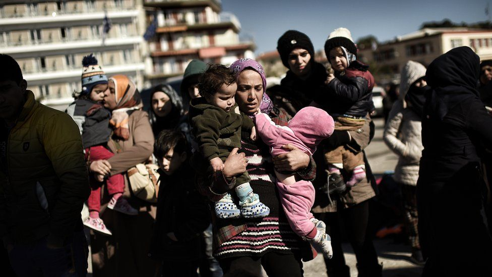Women carry babies after arriving with other refugees and migrants in Mytilene, the port of the northern island of Lesbos, on 22 February 2016