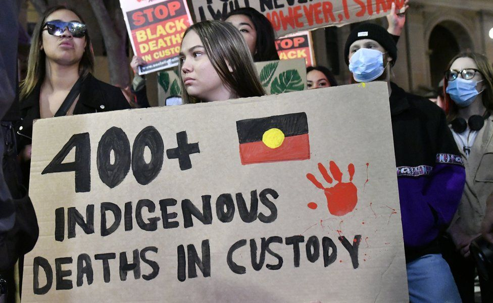 A protester at Sydney's Black Lives Matter march holds up a sign which reads '400 indigenous deaths in custody'