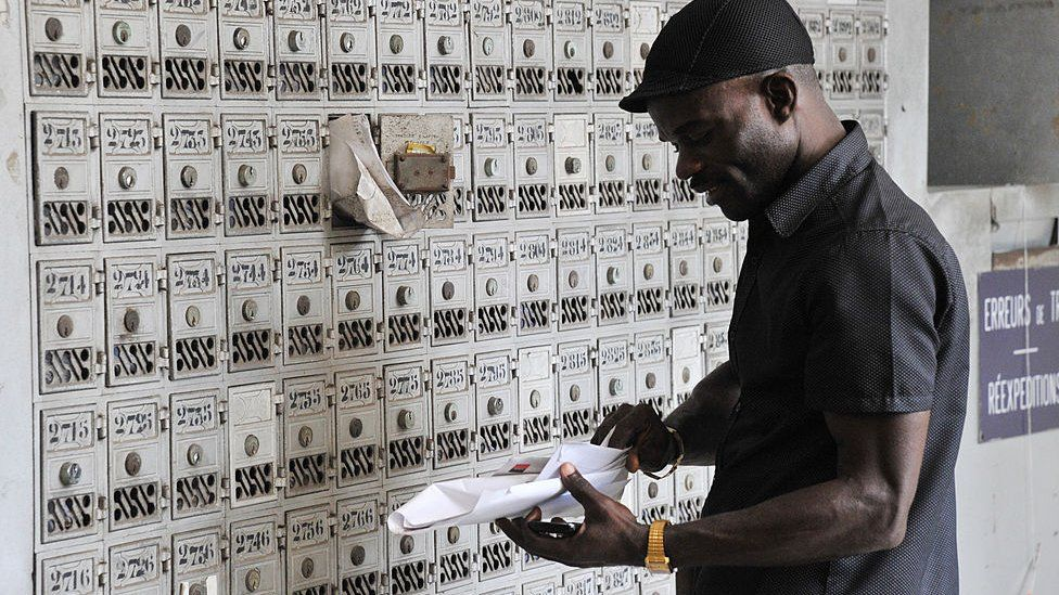 A man collecting mail from his post office box in Abidjan, Ivory Coast