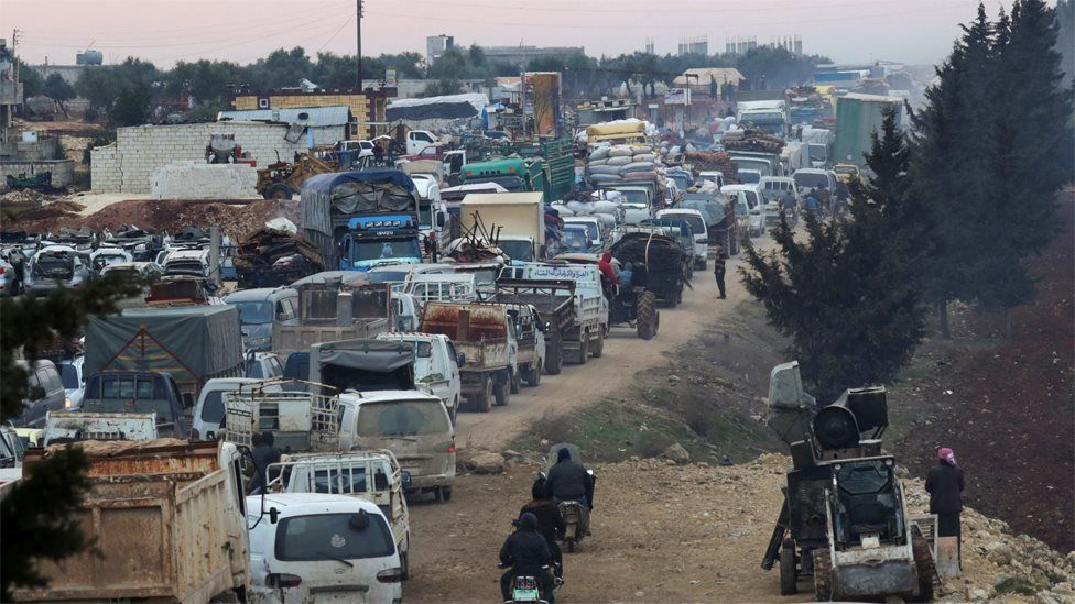 Displaced Syrians travelling in vehicles queue to pass through the town of Sarmada in Idlib province (28 January 2020)