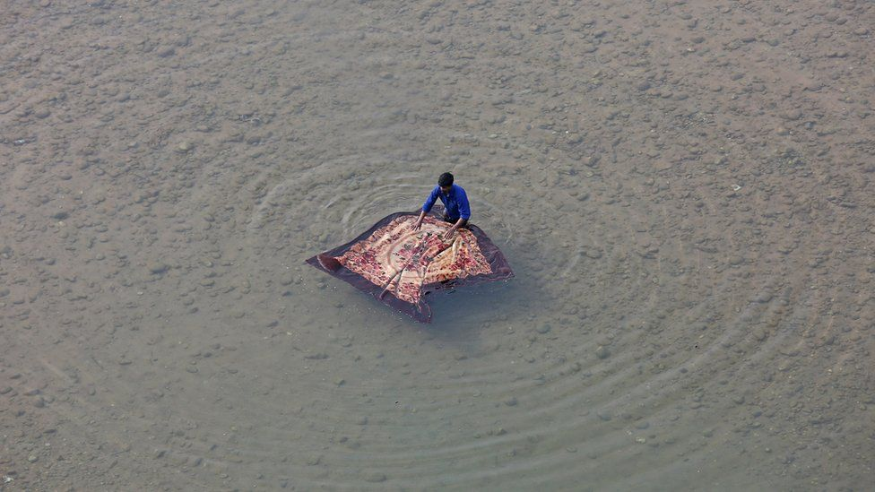 A man washes a blanket on the banks of the river Tawi in Jammu on 28 November 2017.