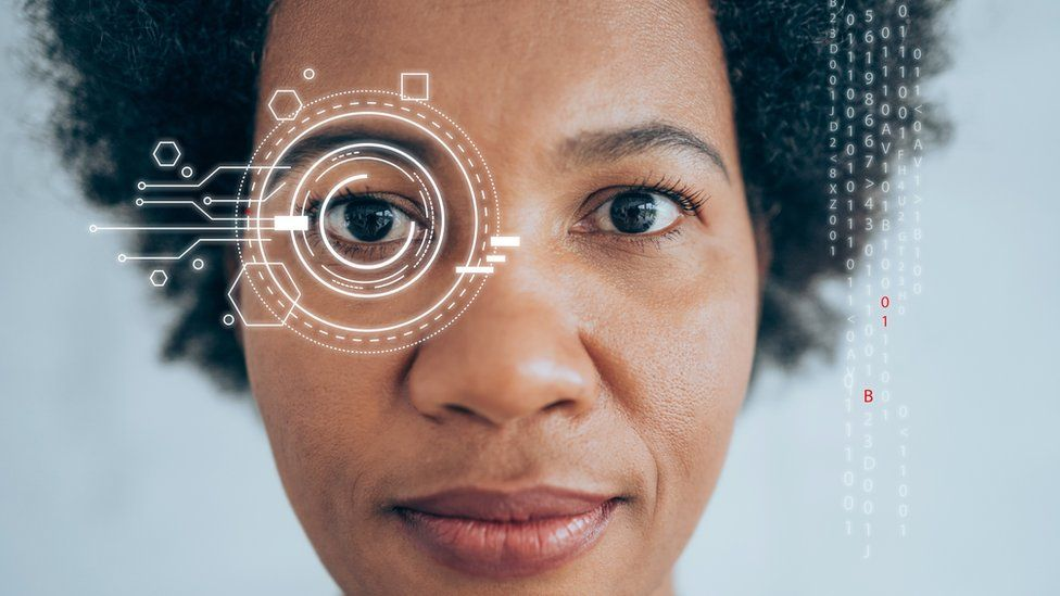 """A black woman looks directly into the camera lens in a photo with overlaid graphics indicating """"scanning"""""""