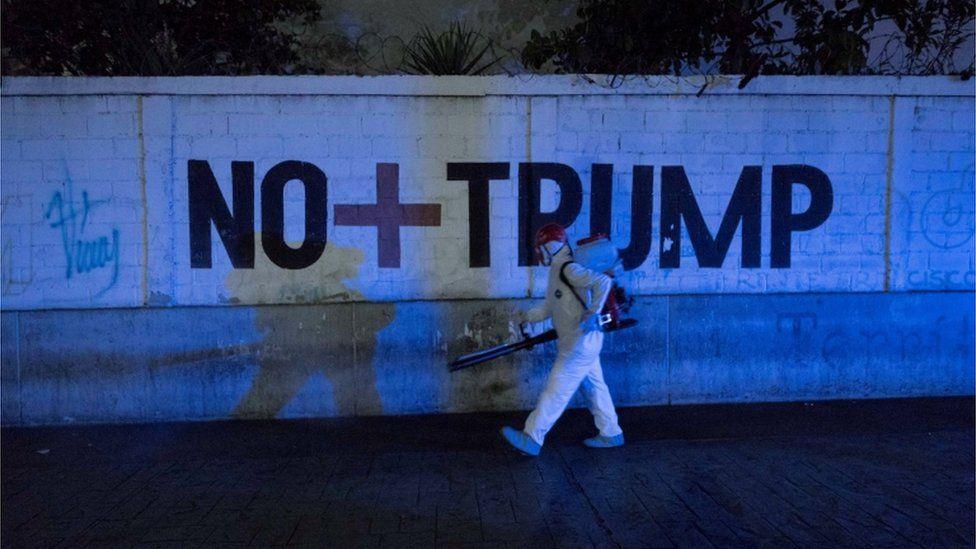 A man walks past graffiti reading No more Trump