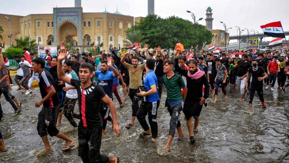 Anti-government protesters march through flood waters in the city of Najaf