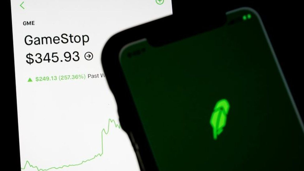 Trading information for GameStop is displayed on the Robinhood App as another screen displays the Robinhood logo in this photo illustration