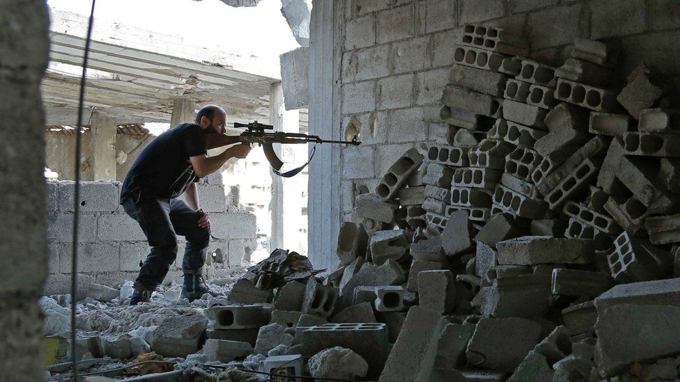 Syrian rebel fighter from the Faylaq al-Rahman brigade fires a weapon in the Eastern Ghouta area on July 17, 2017