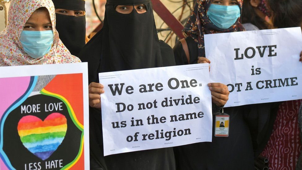 """Activists belonging to various human and civil rights organisations hold placards during a demonstration condemning the decision of various Bharatiya Janata Party (BJP) led state governments in the country for the proposed passing of laws against """"Love Jihad"""" in Bangalore on December 1, 2020."""