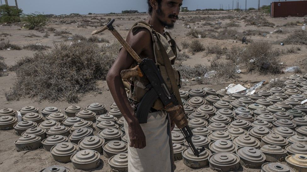 File photo showing a Yemeni pro-government fighter standing next to landmines that were laid by Houthi rebel fighters in al-Himah (22 September 2018)