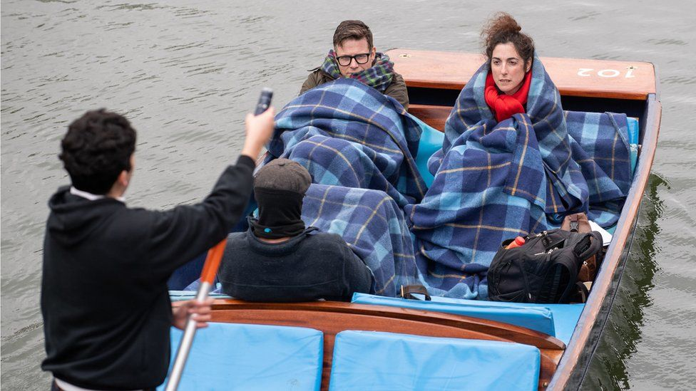 People wrap in blankets as they take a punt tour along the River Cam in Cambridge