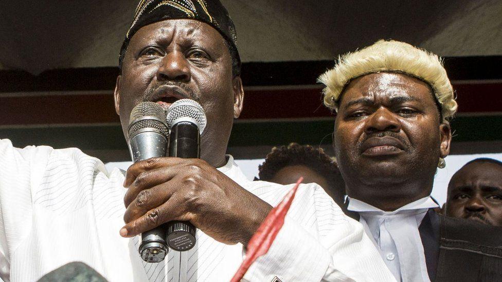 Raila Odinga addresses the crowd with Tom Kajwang standing behind him