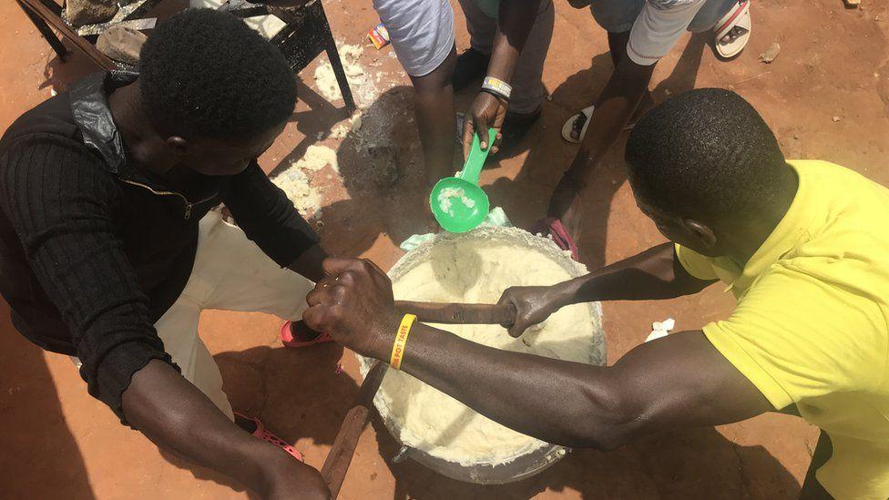 People cooking the semolina in a huge pot