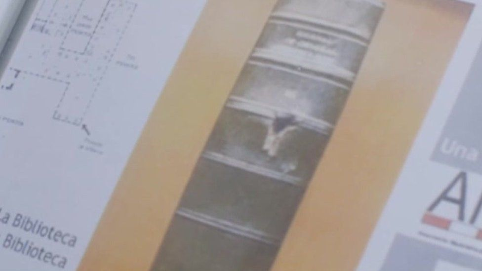 A photograph of a bullet hole in the spine of a book