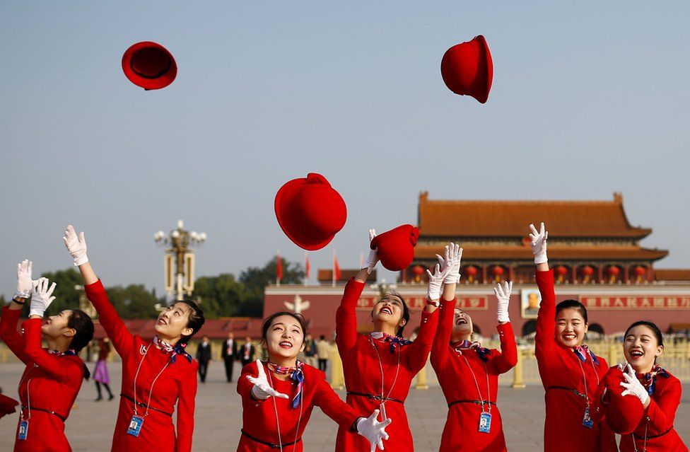 Ushers throw their hats in the air as they pose for photographers at the Tiananmen Square.