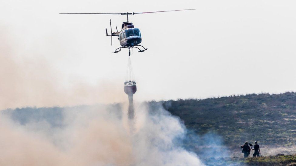 Helicopter drops water on fire