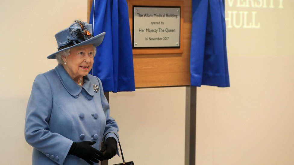The Queen standing in front of a plaque