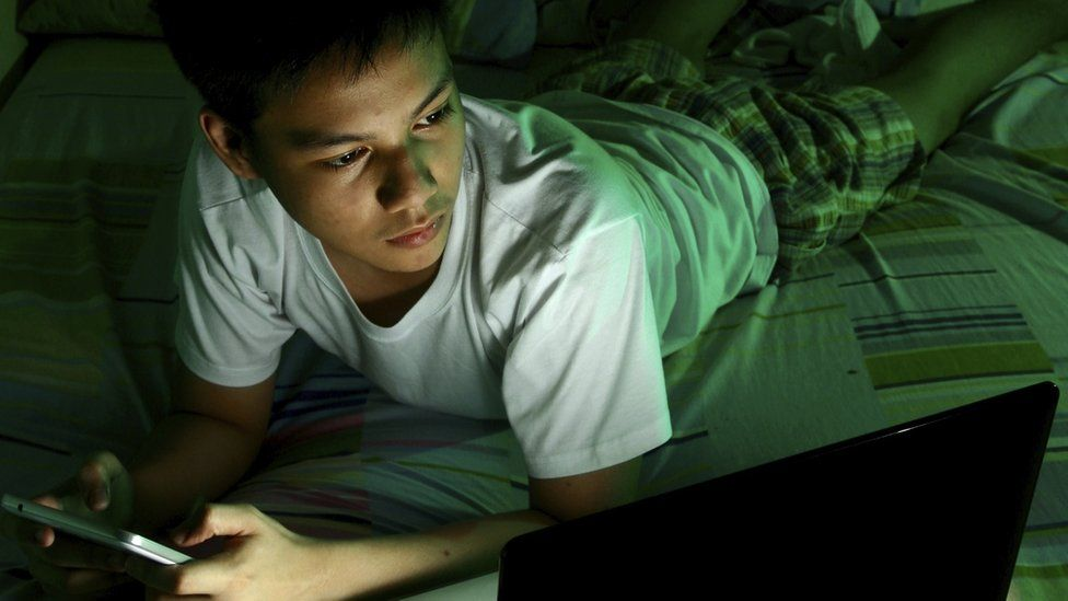Child on bed using phone and laptop