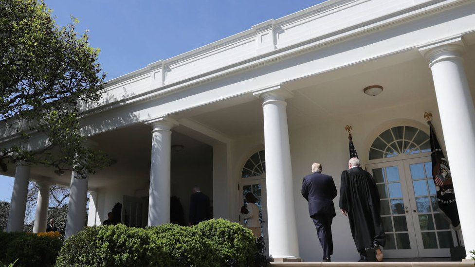 President Donald Trump (L) walks with Supreme Court Justice Neil Gorsuch at the White House.