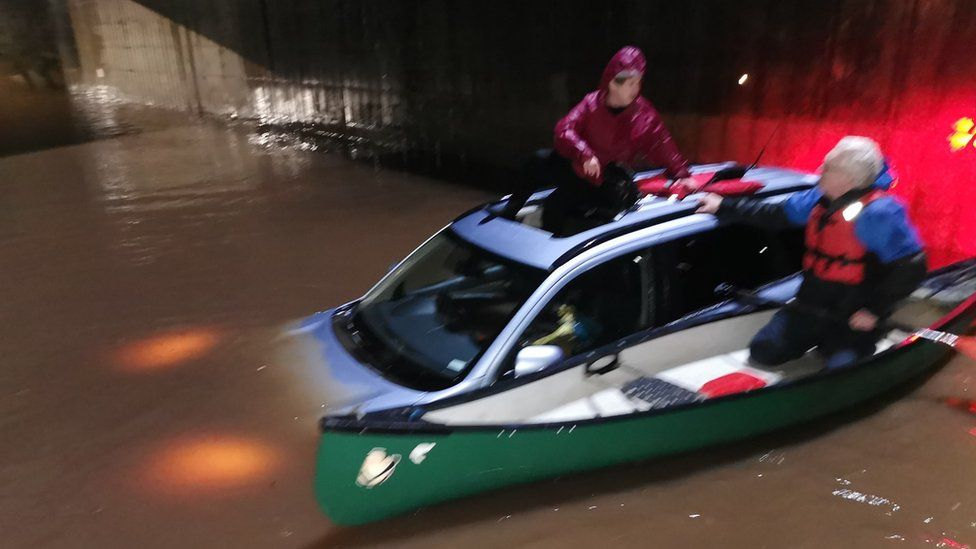 Woman being rescued from car in floodwater