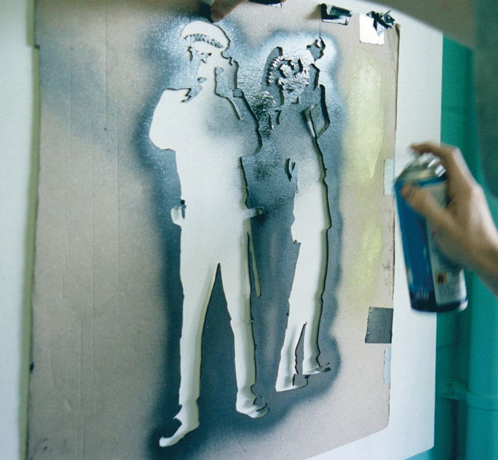 Banksy spraying a stencil