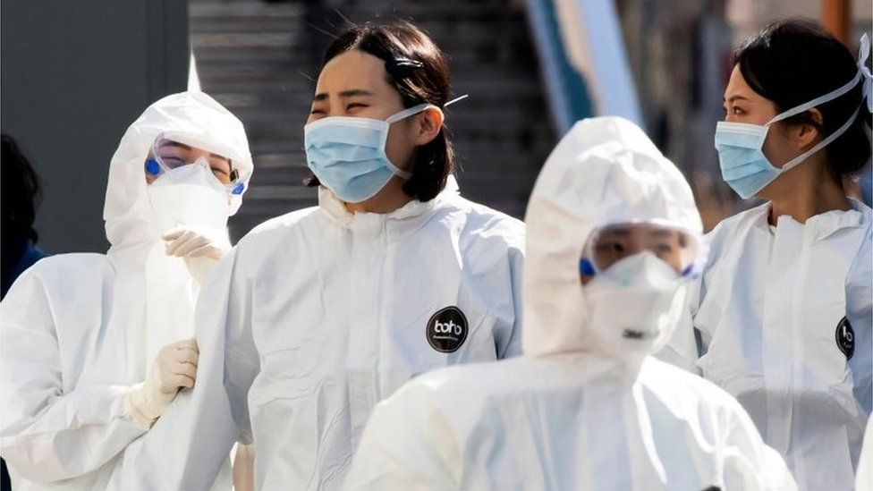 Medical staff members wearing protective gear arrive for their shift to care for patients infected with the COVID-19 coronavirus, at a hospital in Daegu on March 11, 2020.
