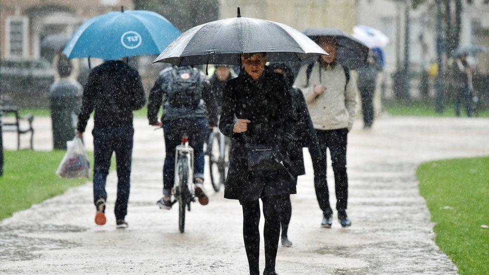 people walk with umbrellas in Bristol
