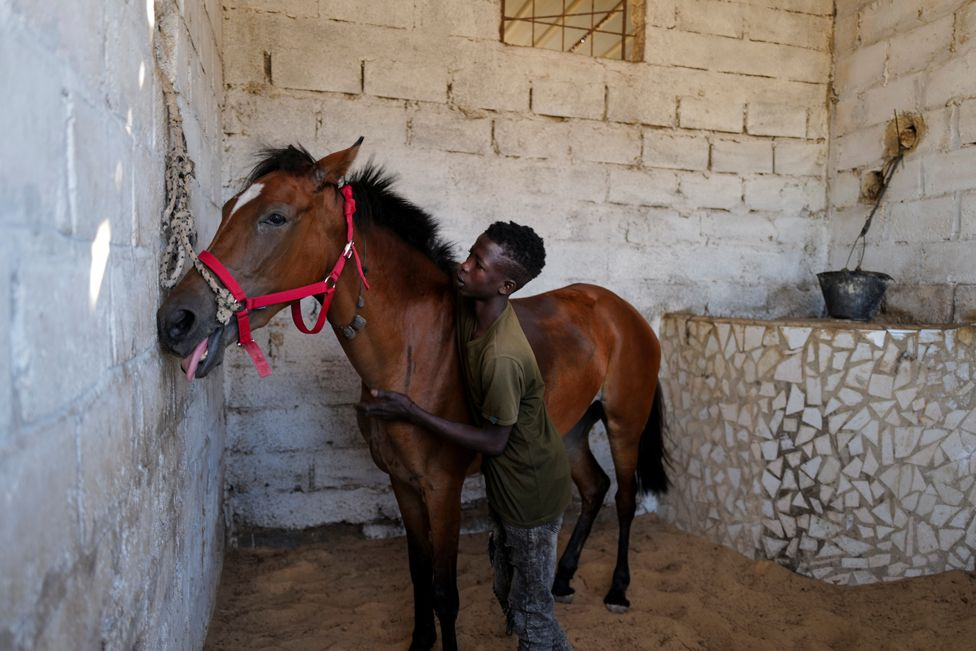 Fallou Diop hugs his horse at the Lambafar stable in Niaga, Senegal, 27 January 2021