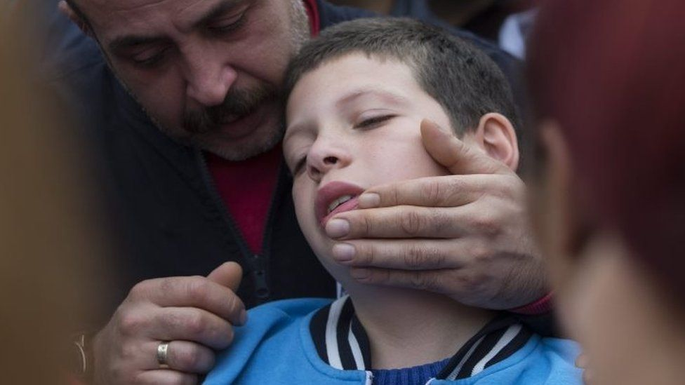 Mourners at an Istanbul funeral try to comfort nine-year-old Cayan, whose father was killed in Ankara