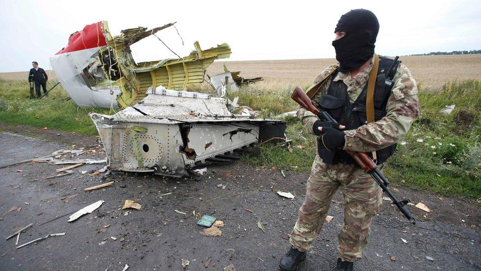 A pro-Russian separatist standing at the crash site of Malaysia Airlines flight MH17, near the settlement of Grabovo in the Donetsk region (18 July 2014)