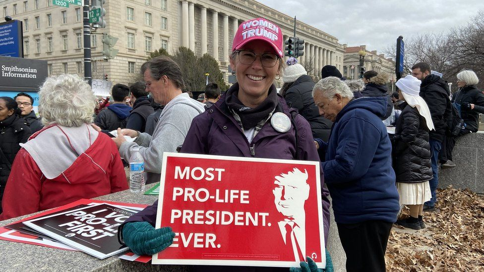 Sarah Schultz holds sign reading 'most pro-life president ever'