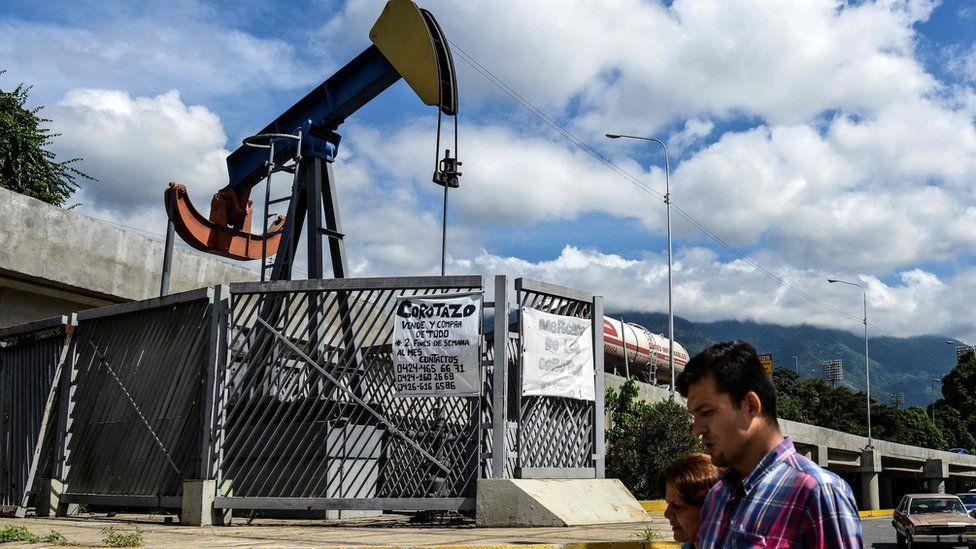 People walk by oil pump in Caracas on November 14, 2017